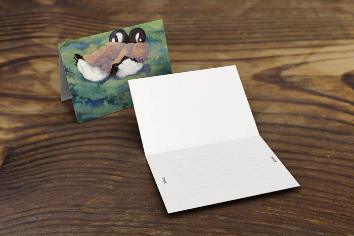 Greeting card or note card opened on table with blank inside, Canada geese on green landscape